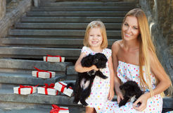 Cute little girl and her mother hugging dog puppies Stock Photography