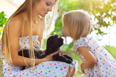 Cute little girl and her mother hugging dog puppies Royalty Free Stock Photography