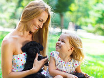 Cute little girl and her mother hugging dog puppies Stock Photo