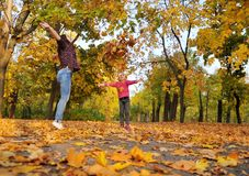 Cute little girl and her mother plays with an autumn leaves. stock photos
