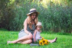 Cute little girl with her mother walking in the park, sunflowers. Family look sunset summer stock photo