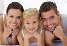 Cute little girl with her parents lying on a bed Royalty Free Stock Photo