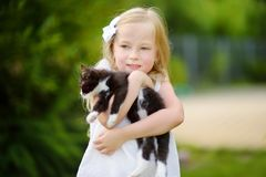 Cute little girl with her pet kitten on summer day. Kids and animals. Royalty Free Stock Photography