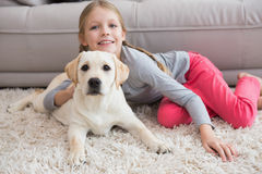 Cute little girl with her puppy on couch Stock Images