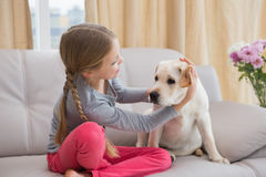 Cute little girl with her puppy on couch. At home in the living room Royalty Free Stock Photography