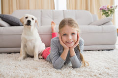 Cute little girl with her puppy on rug Royalty Free Stock Photo