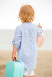 Cute little girl with her suitcase at the sea Royalty Free Stock Images