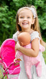 Cute little girl with her toy carriage and doll Stock Photos