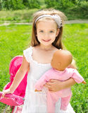 Cute little girl with her toy carriage and doll Royalty Free Stock Photos