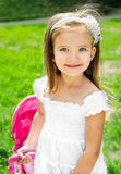 Cute little girl with her toy carriage and doll Royalty Free Stock Images
