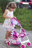 Cute little girl with her toy carriage and doll outdoors Stock Photos