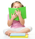 Cute little girl is hiding behind a book stock photo