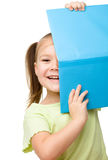 Cute little girl is hiding behind a book Stock Photos