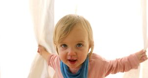 Cute little girl hiding behind a curtain. Looking out and having fun. Happy child playing hide and seek stock video footage