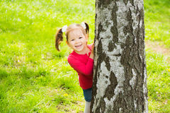 Cute little girl hiding behind huge tree Stock Photography