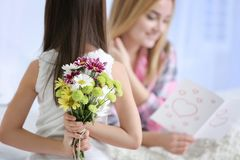 Cute little girl hiding flowers for her mother behind back. Close up. Mother`s day concept Stock Image