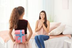 Cute little girl hiding gift box for mom behind her back. Indoors. Mother`s day celebration Royalty Free Stock Image