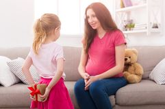 Girl hiding gift from mother behind her back. Cute little girl hiding gift from her pregnant mother behind her back. Mothers Day celebration, daughter Stock Photo