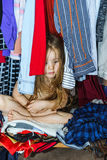 Cute little girl hiding inside wardrobe from her parents. Early morning Stock Photos