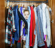 Cute little girl hiding inside wardrobe from her parents. Early morning Stock Photography