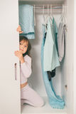 Cute little girl hiding in wardrobe Stock Photo