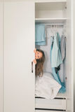 Cute little girl hiding in wardrobe Stock Images