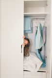 Cute little girl hiding in wardrobe Stock Image