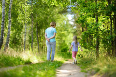 Cute little girl hiking in a forest with her grandmother on beautiful summer day Stock Image