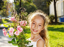 Cute little Girl hold roses and smile at summer day outdoors Stock Photo