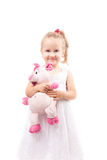 Cute little girl hold toy pig isolated. Cute little girl in white dress hold toy pig isolated Stock Photography