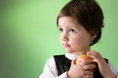 Cute little girl holding apple. Studio shot Royalty Free Stock Images