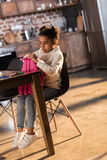 Cute little girl holding backpack while sitting at table with felt tip pens Stock Photos