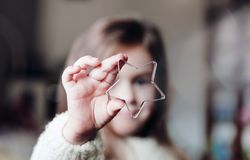 Cute little girl holding big christmas star and looking through it. Christmas holiday portrait royalty free stock image