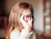 Cute little girl holding big christmas star and looking through it. Christmas holiday portrait royalty free stock images