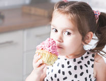 Cute little girl holding birthday cupcakes in kitchen. Festive and holiday concept stock photography