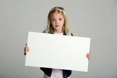 Cute little girl holding a blank sign on gray