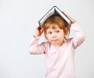 Cute little girl holding book on head Stock Photo