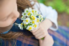 Little girl holding a bouquet of daisies in the spring. Cute little girl holding a bouquet of daisies in the spring stock image