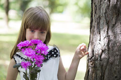 Cute little girl holding a bouquet of flowers in hand and enjoy. Cute little girl holding a bouquet of flowers in hand, enjoy nature and beautiful day Stock Images