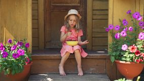 Little Girl Eating Fresh Strawberry in Summer Day. Cute Little Girl Holding a Bowl Full of Fresh Strawberry on her Knees while Sitting on the Porch of a Country stock footage