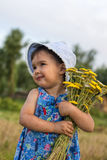 Cute little girl holding an bucket of  yellow yarrow flowers Royalty Free Stock Photos
