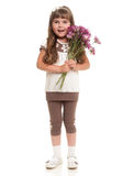Cute little girl holding the bunch of flowers. Against white background Royalty Free Stock Photos