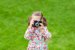 Cute little girl holding camera and taking photograph outdoors. Royalty Free Stock Photos