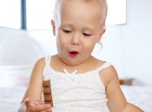 Cute little girl holding chocolate. Close up portrait of a cute little girl holding chocolate Stock Photo