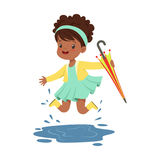 Cute little girl holding colorful umbrella and playing in the rain cartoon vector Illustration Royalty Free Stock Photos
