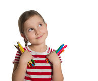 Cute little girl holding colourful pencils and markers looking u Stock Photos