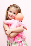 Cute little girl holding and embracing her doll Royalty Free Stock Photography
