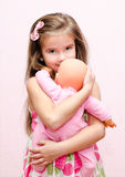 Cute little girl holding and embracing her doll Stock Photography