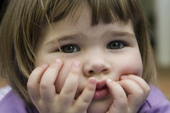 Cute little girl holding face Stock Images