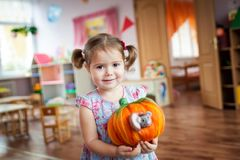 Cute little girl holding felt pumpkin toy. Vibrant background Stock Image